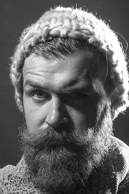 picture of hobo  - Portrait of strange unshaven male hobo with long beard and hendlebar moustache in knitted hat and scarf looking forward arching brow black and white closeup vertical picture - JPG