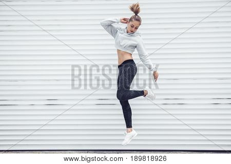 poster of Fitness sporty girl in fashion sportswear dancing hip hop in the street, outdoor sports, urban style