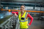 Portrait of smiling female factory worker standing next to production line at drinks production fact poster
