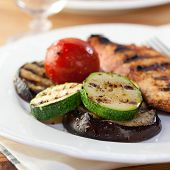 Grilled vegetables and chicken breast on a white plate
