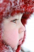 Winter baby. One year old baby dressed in warm clothing. Baby with snowflakes on his cap.