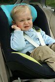 18 months old baby boy in car safety seat. Unhappy child crying.