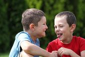 Portrait of two boys, siblings, brothers and best friends giggling and making faces.