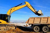 Excavator loading dump truck tipper at open cast over blue sky in winter