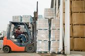 forklift loader at warehouse outdoors stacking cardboard boxes on pallet to stockpiles