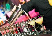 barman?s hand with shake mixer pouring cocktail into glasses arranged in a line