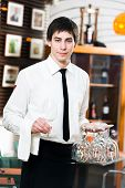 handsome man waiter in uniform at restaurant