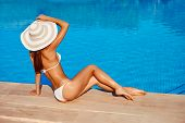 Portrait Of Beautiful Tanned Sporty Slim Woman Relaxing In Swimming Pool Spa. Creative White Hat And poster