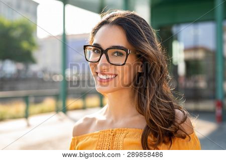poster of Portrait of carefree young woman smiling and looking at camera with urban background. Cheerful latin