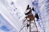 Telecomunication antenna under clouded sky.