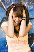 Screaming young woman over blue background