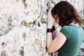 Young female prayer against stone wall.