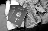 Getting Ready To Travel - black and white image of passports and clothing in a suitcase