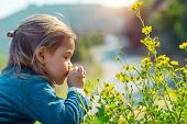 Little boy enjoying flowers aroma, with pleasure with closed eyes smelling gentle yellow wild flower poster