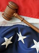 Judicial System - wooden gavel atop portion of American flag
