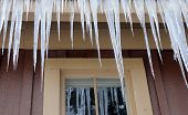Icicles hanging down from a building - frigid and frozen weather themes.