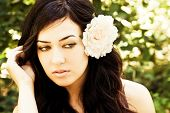 Young beautiful woman with a white rose on her hair.