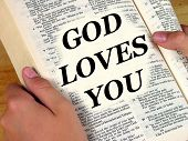 A person holding a bible. The words 'God Loves You' appear out of the scriptures.