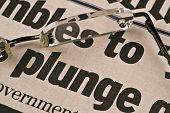 Dow taucht Closeup Bild der Zeitung und Lesebrille. schlechte Nachrichten aus der Wirtschaft