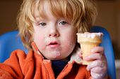 foto of child obesity  - a young boy eating an ice cream cone - JPG