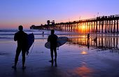 Surfers watch an Oceanside California sunset. Pacific Ocean in Southern California near sunny San Diego.