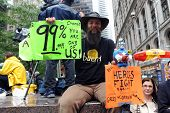 MANHATTAN, NY - SEPT. 18: A man holds signs in Zuccotti Park as part of the 'Occupy New York' Protes