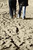 A couple walking together on sand toward their destination. Blur on foot movement is visible. poster