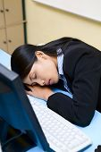 A young woman is sleeping in front of her computer.
