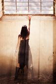Gothic young woman raising hand towards light.