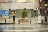Joven rubia esperando en la parada del tráfico bajo la lluvia
