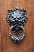 Ancient italian door knocker on wooden door background. poster