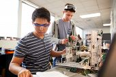 Two Male College Students Building Machine In Science Robotics Or Engineering Class poster