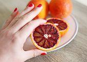 Hand Holding Fresh Oranges - Tarocco Blood Orange - Sanguine Orange - Red Orange poster