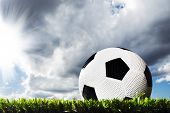 Close up of a soccer ball on a soccer field ready for kick off - under heavy clouds with sun breakin