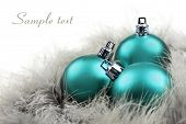 Colorful blue christmas ornaments on a white background with space for text