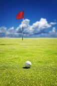 Bola de golfe no verde pronto para ser tacada no buraco - profundidade de campo