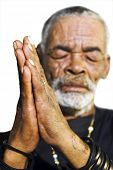 An old African man with folded hands - focus on the weathered hands on a white background with space for text