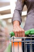 Cropped image of woman holding pushcart at supermarket