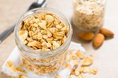 Homemade Baked Crunchy Oatmeal, Sliced Almond, Honey And Coconut Oil Breakfast Granola In Glass Jar, poster