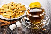 Bread Sticks With Poppy In White Plate, Lemon, Cinnamon Sticks, Cup Of Tea, Teaspoon On Saucer, Suga poster
