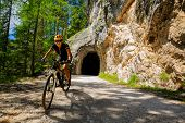 Woman mountain bike rider on electric bike, e-mountainbike rides up mountain trail. Woman ride on e- poster