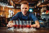 Male bartender prepares four beverages in glasses poster