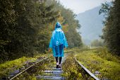 Girl Traveller Wearing Blue Jacket And Go By Forest Railway. Autumn And Raining Season With Dark Gre poster