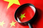 The Flag Of The Chinese Peoples Republic Is Looking Through A Magnifying Glass. The Study Of The His poster