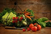 Freshly picked vegetables on metal basket in wooden table