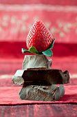 Strawberry Balancing On A Pile Of Dark Chocolate