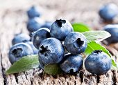 Blueberries with leaves on a old wooden table.