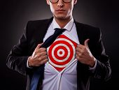 stock photo of superman  - Young business man showing a target under his shirt on dark background - JPG