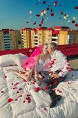 The newly married couple in rose petals on the roof of house in the morning
