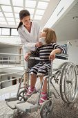 stock photo of neck brace  - Doctor talking to chld with neck brace in wheelchair in hospital corridor - JPG